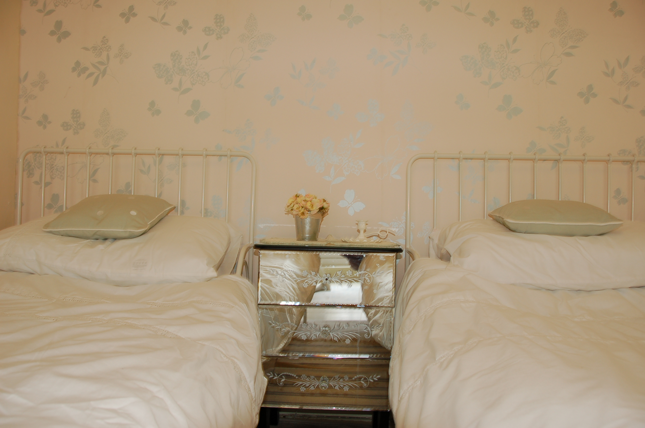 pretty twin beds look out towards the garden at Periwinkle